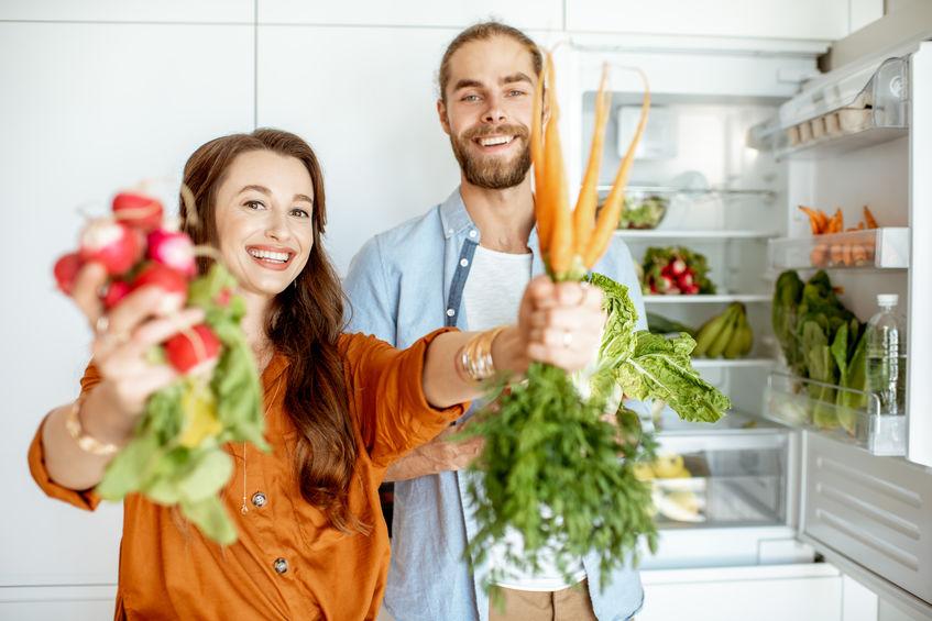 Jong koppel met gezonde voeding in de keuken