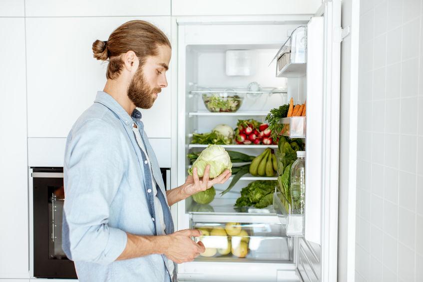 Man pakt sla uit koelkast op zoek naar bronnen van collageen