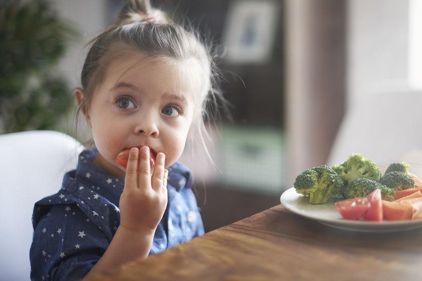 klein meisje dat wat aardbeien eet